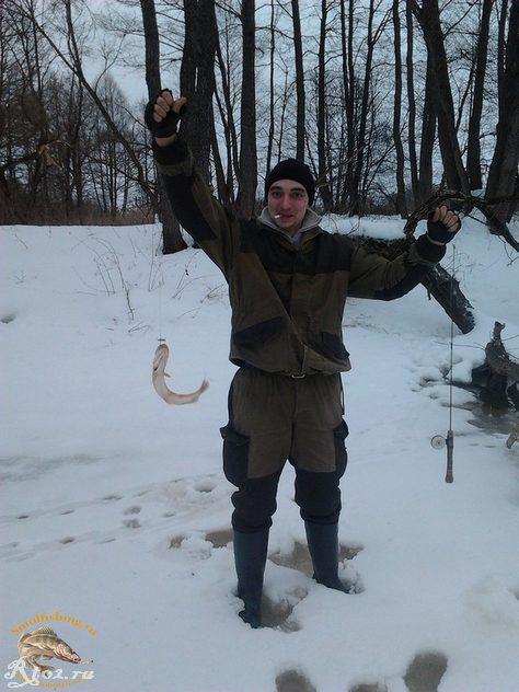брат поймал щуку на реке зимой
